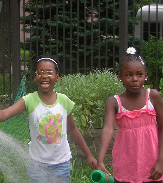 girls playing in water hose